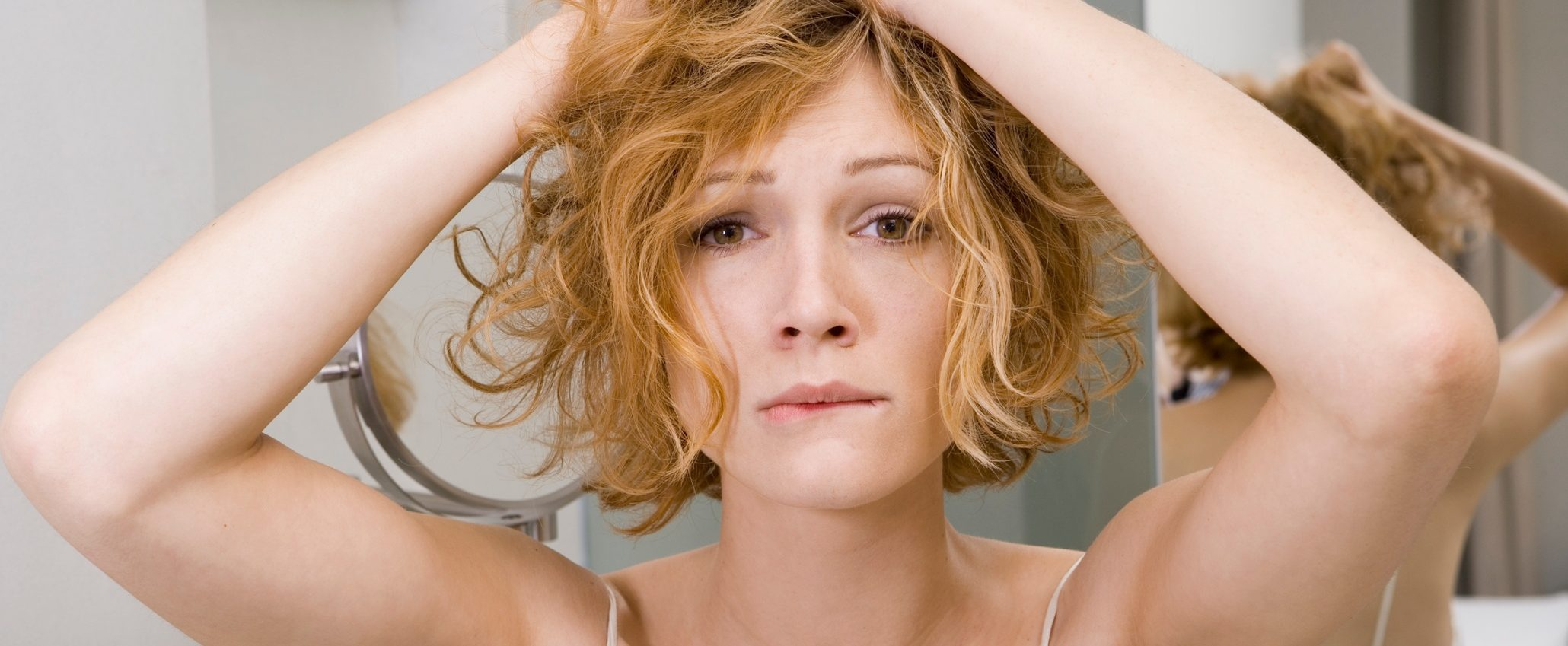 Woman in bathroom tearing her hair out