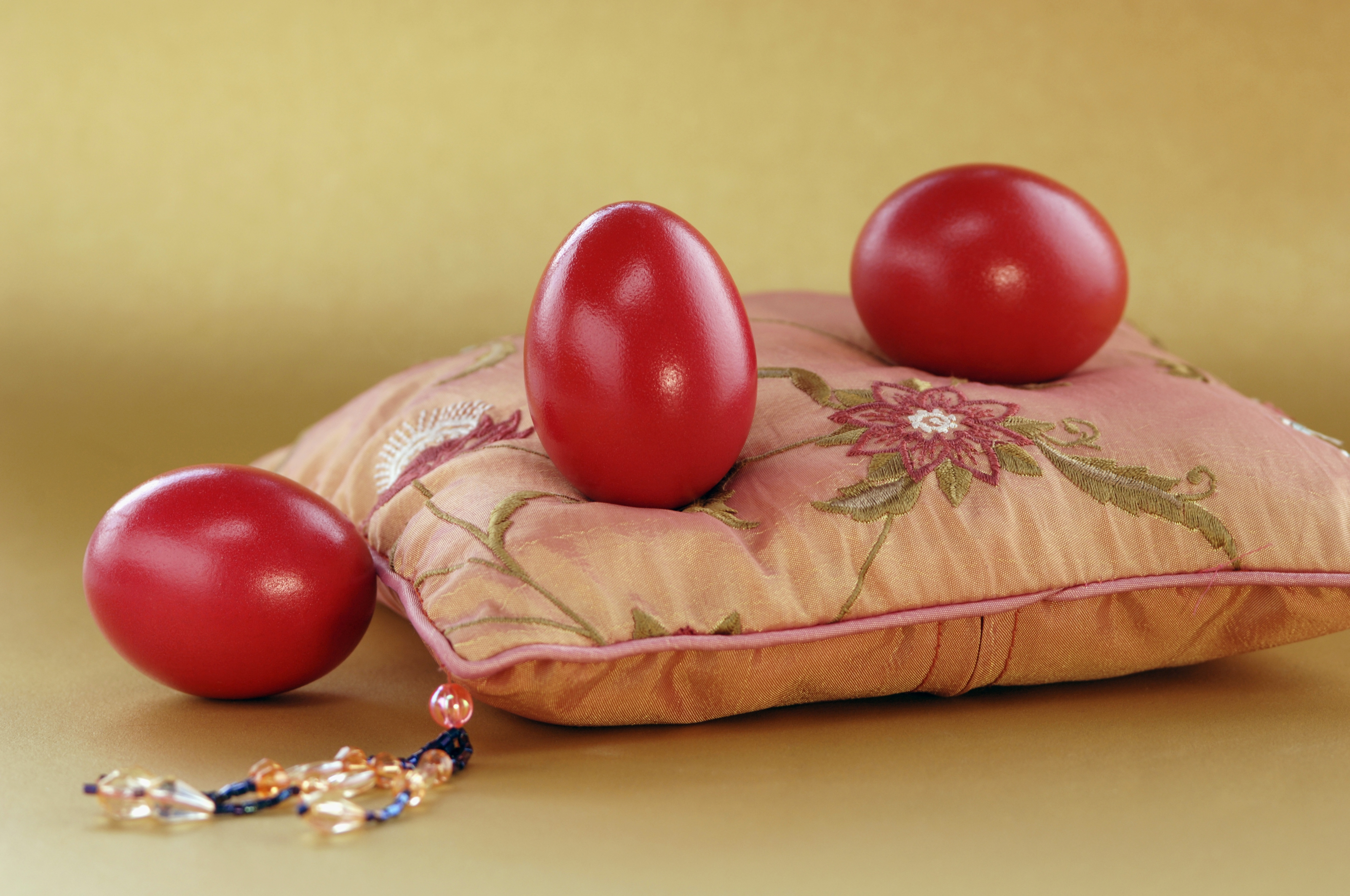 Red Easter eggs on pink pillow, close-up